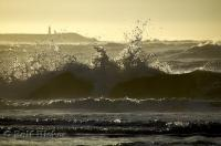 The crashing ocean waves of the Pacific Ocean with the Destruction Island Lighthouse in the background.