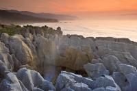The sun sets over the Tasman Sea and the Pancake Rocks in Paparoa National Park on the West Coast of New Zealand.