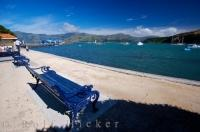 Relax on a park bench along the waterfront in the town of Akaroa in Canterbury on the South Island of New  Zealand and take in the scenery.