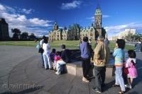 Under the blue sky of Ottawa, Ontario visitors take pictures of the Parliament building atop Parliament Hill.