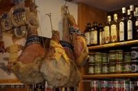 Delicious Prosciutto from Parma hanging beside shelves of bottles, jars and cans in a shop in Venice, Italy.