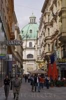 Shops and tourists fill the street in downtown Vienna, Austria with the Peterskirche prominently standing at the end.