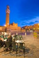 As people sit outside a cafe enjoying the ambiance and architecture of Piazza Del Campo, the Torre del Mangia and Palazzo Pubblico are lit up as dusk falls on the historic old town district in Siena; a UNESCO World Heritage Site.