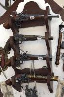 On a wooden rack hanging on the wall in a shop in the Karlstein Village in the Czech Republic, a pistol display intrigues tourists.