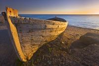 An old abandoned wooden boat along Playa de San Miguel del Cabo de Gata is bathed in the golden light of the afternoon sun along the Costa de Almeria. Playa de San Miguel is situated in the Parque Natural de Cabo de Gata in the Province of Almeria.