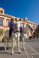 Two policemen riding on horseback outside the Palacio Arzobispal in the Plaza Virgen de los Reyes in the City of Sevilla in Andalusia, Spain in Europe.