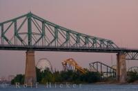 As the faint tinge of pink light floods the sky that signals the end of another day, the Jacques Cartier Bridge (Pont Jacques-Cartier) with La Ronde amusement park in the background can be seen clearly in the city of Montreal, Quebec, Canada.