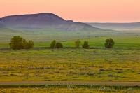 A medley of colours, vivid pinks and fresh greens, adorn the scenery of the Saskatchewan prairie which is punctuated by the Big Muddy Badlands.