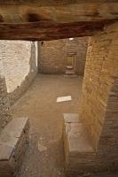 A room or chamber which leads to a series of doors is entered under a wooden transom and beside what looks like a pair of stone seats at Pueblo Bonito, Chaco Culture National Historic Park.