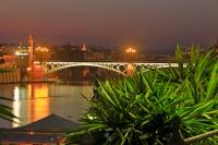 The Puente de Isabel II (bridge) crosses the Rio Guadalquivir (River) is lit up at dusk in the city of Seville in Andalusia, Spain. This bridge crosses over to the Triana district in the city and the bridge is still in use today.