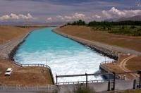 The control gates are opened and Lake Pukaki drains into the river canal in Canterbury, New Zealand.