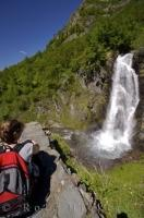 A beautiful waterfall streams over the rocks on the slopes of a mountain in the Aran Valley in the pristine Pyrenees Mountains - a popular tourist destination in the region of Catalonia, Spain.