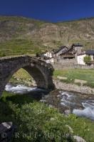 An ancient stone bridge crosses over the Riu Escrita into the village of Espot in Catalonia, Spain.