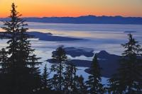 A beautiful aerial shot over Queen Charlotte Strait from Northern Vancouver Island during sunset, looking towards the coast mountains of the British Columbia mainland.