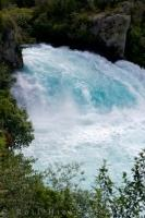 Watching from a viewpoint, the water is raging over the Huka Falls along the Waikato River on the North Island of NZ possessing a unique blue coloring.