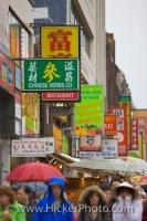 The street of Chinatown in Toronto, Ontario is full of people who love shopping even on a rainy day when umbrellas are required.