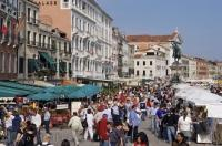 The Riva degli Schiavoni markets along the waterfront in the city of Venice, Italy welcome the visiting crowds of people.