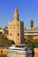 One of the many tourist tours are starting by boat in front of the Torre del Oro on the Rio Guadalquivir in Seville, Spain.