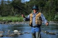 A visitor staying at the world class Tuckamore Lodge in Newfoundland, Canada enjoys fly fishing in nearby Trout River.