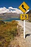 Along the roadside to Lake Hawea in Central Otago on the South Island of New Zealand, a sign warns travellers to slow down due to the winding road.