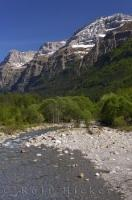 The rock banks of the Cinca River which are towered over by the high mountain peaks in Parque Nacional Ordesa y Monte Perdido in the Pyrenees in Huesca, Aragon in Spain.