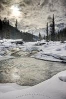 The Mistaya River is flowing freely despite the ice and snow lying on the ground all along its banks. This area of the Rocky Mountain Parks is known for its stunning year round scenery from the cold of winter to the warmth of summer.