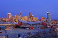 The Calgary Saddledome begins to light up at sunrise as the city comes to life, as can be seen here in this picture of the city of Calgary in Alberta. The Saddledome is one of the most recognizable structures in this Cowboy city.