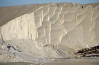 A salt cliff looms over the equipment used in this type of industry in the Parc Naturel Regional de Camargue in Provence, France.