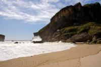 A beautiful summer scene of soft sand and the constant waves of the Tasman Sea lapping at the shores of Kohaihai Beach on the West Coast of New Zealand's South Island. This beach, situated near the town of Karamea, is the start of the famous Heaphy Track.