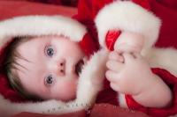 A cute baby dressed in a santa outfit lying on his side with hands together.