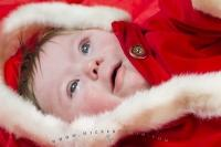 An angelic picture of a baby dressed in a santa costume on Christmas Day.