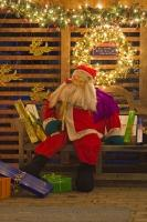 A mannequin dressed up like santa - placed on a park bench and surrounded by gifts and sparkling lights forms part of a christmas display outside a house.