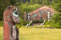 A old Totem Pole in front of a long house in Saxman Totem Park in Ketchikan.
