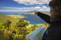With a map in hand a woman points towards some of the coastal scenery of the Marlborough Sounds.
