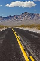 The yellow centre lines of this desert country road lead the eye towards the scenic Black Mountains in Death Valley National Park in California.