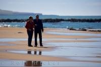 A couple of seniors take a beach walk at Waipapa Point in New Zealand as part of their relaxing sun filled beach vacation. This beach is found in the Catlins along the Catlin's Highway on the East Coast of the South Island of New Zealand.