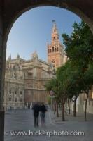A view of the architecture of the Seville Cathedral and La Giralda from a doorway of the Real Acazar in the City of Sevilla in Andalusia, Spain.