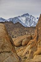 A view from amongst the rock formations of the Alabama Hills, looking towards the snow covered mountains of the Sierra Nevada.