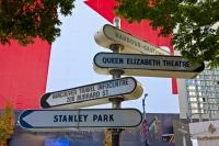 A post full of directional signs, directs pedestrians towards some of the main sights and information centre in downtown Vancouver, British Columbia, Canada.
