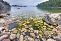 With fog hovering in the distance, the crystal clear and calm water of Lake Superior reveals the rocky shoreline of Sinclair Cove in Lake Superior Provincial Park of Ontario, Canada.