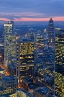 The skyline of the Frankfurt financial district is lit up both by the sunset and the lights of the buildings as another day ends for the workers in the financial sector. The Messeturm and Westendstrasse 1 skyscrapers are known for their height.