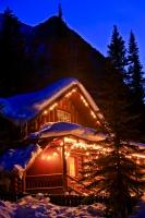 A real winter scene of a cabin covered with fresh snow lit up by decorative lights which give the cabin a sense of coziness and warmth despite the cold surroundings of winter.