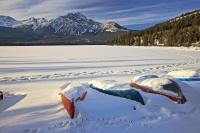 A row of snow covered canoes along the shoreline of Pyramid Lake near the town of Jasper in Jasper National Park during winter.