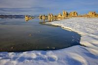 The curved, snow covered shoreline of Mono Lake leads towards a series of tufa towers for which the lake is famous.