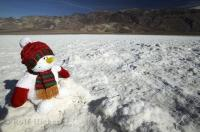 A snowman surrounded by the arid desert landscape makes for some interesting pictures in Death Valley, California, USA.