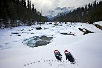 As clouds descend, beginning to cover the peak of Mount Sarbach in Banff National Park, snowshoes are abandoned in the winter snow on the banks of the Mistaya River in the Rocky Mountains.