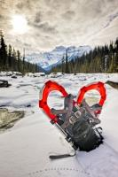 Sitting in the snow banks of the Mistaya River is a pair of snowshoes. To enjoy the winter recreation opportunities, hikers use snowshoes to distribute their weight to help walk on the snow instead of sinking into it.