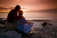 A couple watch the sunset during a romantic getaway at Simcoe Lake in Ontario, Canada.