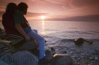 A sunset over Simcoe Lake adds to the romance for this couple on vacation in Ontario, Canada.