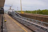 A ship slowly maneuvers into Lock 3 of the Welland Canals System at St Catharines Museum in Ontario, Canada as visitors look on.